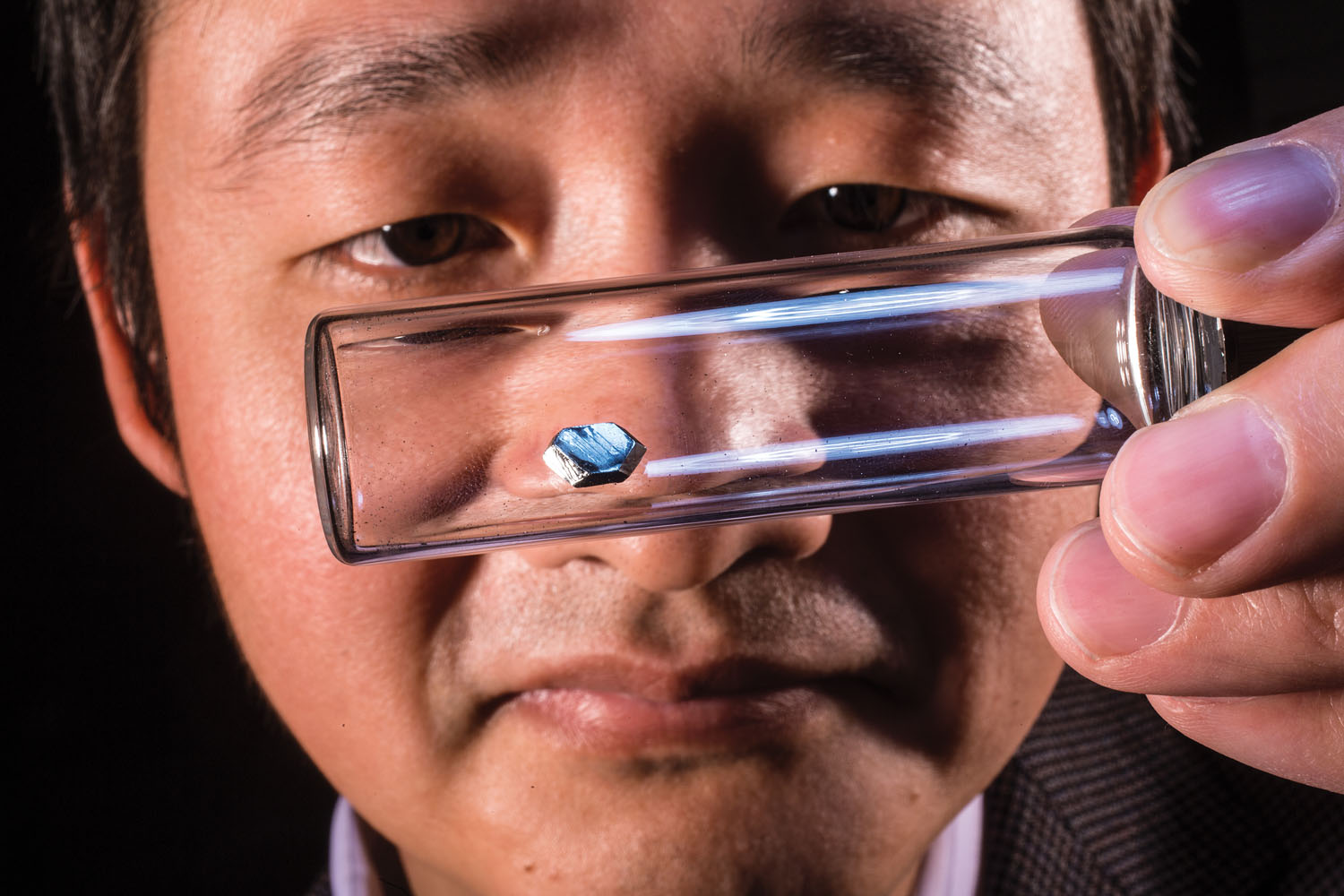 Jinsong Huang inspects a perovskite crystal grown in his UNL lab. The crystal's properties could greatly improve the electrical devices we use.
