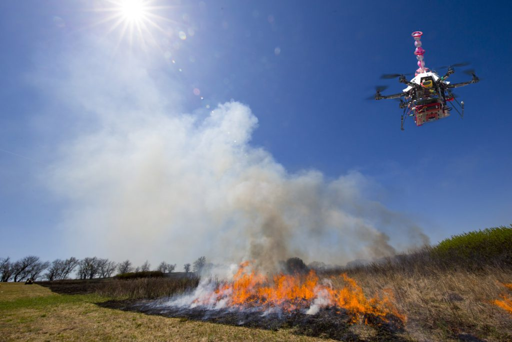 Controlled burn at the Homestead National Monument in Beatrice, NE. Sebastian Elbaum and Carrick Detweiler have engineered a drone able to light controlled prairie burns using balls dropped from the sky. The drone injects a liquid into the plastic spheres to start a delayed fiery process so the balls can fall to the ground before igniting. Elbaum and Detweiler are Professors of computer science and engineering. Twidwell is an assistant professor and range land ecologist in the school of natural resources. April 22, 2015. Photo by Craig Chandler / University Communications